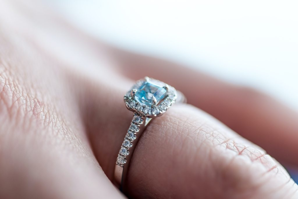 A close-up picture of a hand wearing aquamarine gemstone silver ring.
