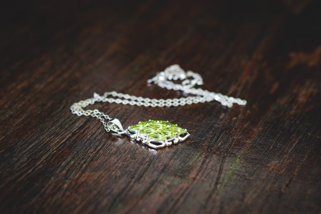 A picture of peridot necklace on wood surface.